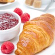 Delicious breakfast - fresh croissant, jam and raspberry — Stock Photo #27425551