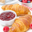Delicious breakfast - fresh croissant with raspberry jam, coffee — Stock Photo #27425561