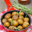 Baked new potatoes with curry and rosemary in skillet — Stock Photo