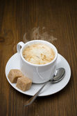 Cup of black coffee with foam and cane sugar cubes — Stock Photo