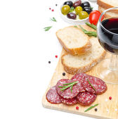 Salami, bread, olives and glass of wine on a wooden board — Stock Photo