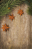 Christmas frame (spruce branches and star anise) on the old wood — Stock Photo