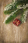Christmas vintage wooden background (spruce branches and gift) — Stock Photo