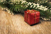 Spruce branch with snow, red gift box on wooden background — Stock Photo