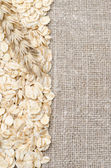 Frame oatmeal and wheat ear on burlap background — Stock Photo