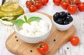 Fresh mozzarella in a bowl, olives and cherry tomatoes — Stock Photo
