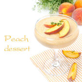 Perzik souffle in glas en fruit in de achtergrond, geïsoleerd — Stockfoto