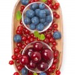 Cherries, blueberries and red currants in a wooden bowl isolated — Stock Photo