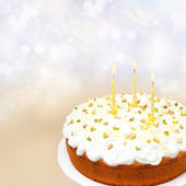 Birthday cake with yogurt icing, andles on colored background — Stock Photo