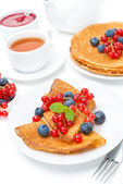 Breakfast with pancakes, fresh berries, jam and black tea — Stock Photo