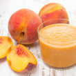 Fresh squeezed peach juice and fresh peaches — Stock Photo
