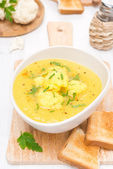 Cauliflower soup with curry in a bowl and toast — Stock Photo