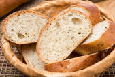 Pieces of baguette with herbs in a basket, close-up — Stock Photo