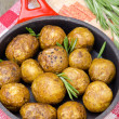 Baked new potatoes with rosemary in a skillet, top view — Stock Photo