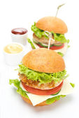Chicken burger with vegetables, cheese and sauces — Stock Photo
