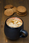 Black coffee with foam and oatmeal cookies on the wooden table — Stock Photo