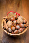 Assorted nuts and spices in a wooden bowl, vertical — Stock Photo