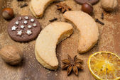 Christmas cookies, spices and nuts on a wooden background — Stock Photo
