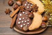 Galletas de navidad, especias y frutos secos en una placa de madera — Foto de Stock