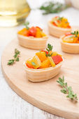 Tartlets with roasted vegetables and thyme on a wooden board — Stock Photo