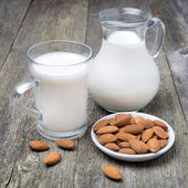 Jug and glass cup with almond milk — Stock Photo