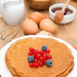 Crepes with berries and ingredients for baking — Stock Photo