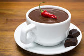 Cup of hot chocolate with chili peppers on a wooden background — Stock Photo