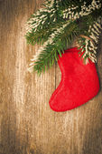 Christmas vintage wooden background (fir branches and red boot) — Stock Photo