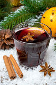 Spicy mulled wine in the glass in the snow, vertical — Stock Photo