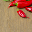 Red hot chili peppers on wooden background (with space for text) — Stockfoto