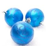 Three blue Christmas balls on snow isolated — Stock Photo #32409011