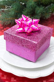 Pink gift box on a plate for Christmas — Stock Photo