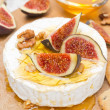 Camembert cheese with honey, figs and walnuts on a wooden board — Stock Photo