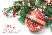 Red Christmas ball, spruce branch and garland, isolated — Stock Photo