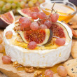 Camembert with grapes, figs, honey and walnuts on a wooden board — Stock Photo