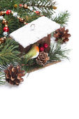Christmas composition with birdhouse and fir-tree branches — Stock Photo