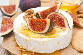 Camembert cheese with honey, figs, walnuts and crackers — Stock Photo
