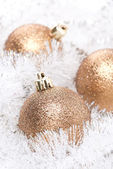 Golden Christmas balls in white tinsel, selective focus — Stock Photo