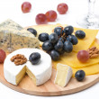 Assorted cheeses, grapes and glass of wine on wooden board — Stock Photo