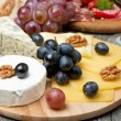 Assorted cheese, grapes, wine and sausages — Stock Photo