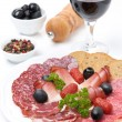 Assorted meat delicacies on a plate, pepper, olives and a glass — Stock Photo