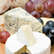Camembert, blue cheese, grapes and walnuts on wooden board — Stock Photo #34638099