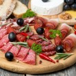 Assorted meats and sausages on a wooden board — Stock Photo