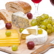 Cheese platter, grapes, bread and red wine on a wooden board — Стоковая фотография