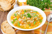 Plate of vegetable minestrone with white beans and toast — Stock Photo