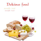 Cheese platter, grapes, ciabatta and two glass of red wine — Stock Photo
