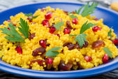Couscous salad with curry, dried cranberries and herbs, close-up — Stock Photo