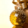 Transparent Christmas ball and gift box on a golden background — Zdjęcie stockowe