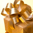 Stock Photo: Christmas gift box on golden background