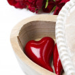 Red heart in a wooden box and roses — Stock Photo